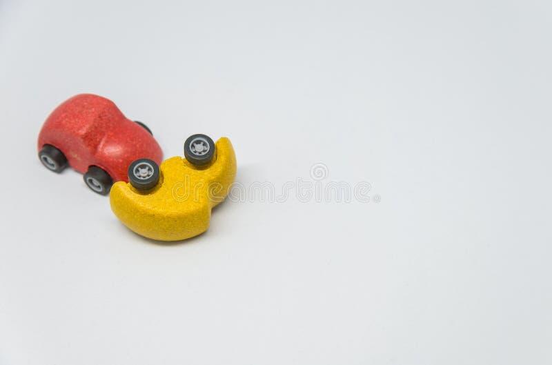 De rode stuk speelgoed auto verpletterde geel stuk speelgoed autoongeval met witte achtergrond royalty-vrije stock afbeelding