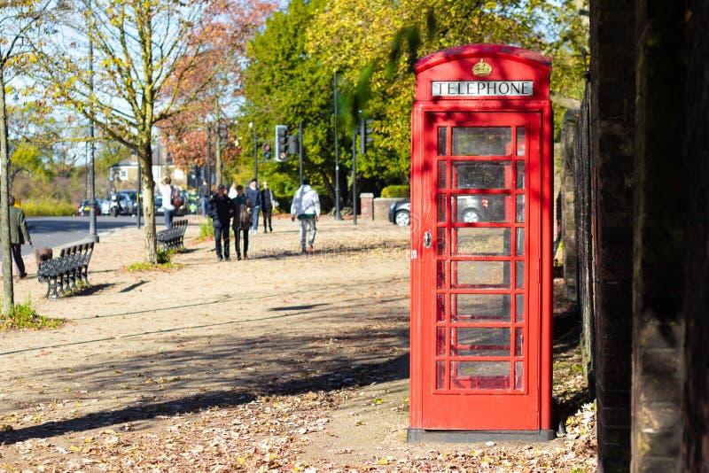 De rode telefooncel van Londen in een park stock afbeeldingen