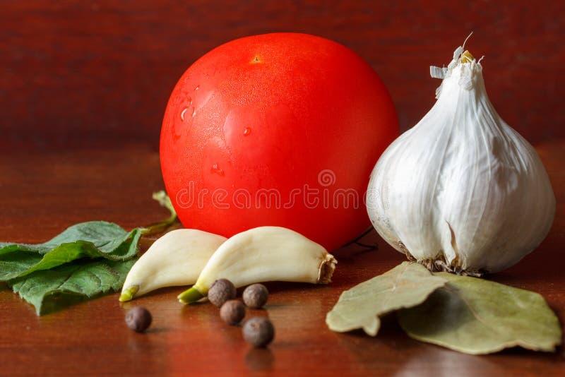 De rode tomaat en het knoflook met kruiden zijn op de lijst stock foto