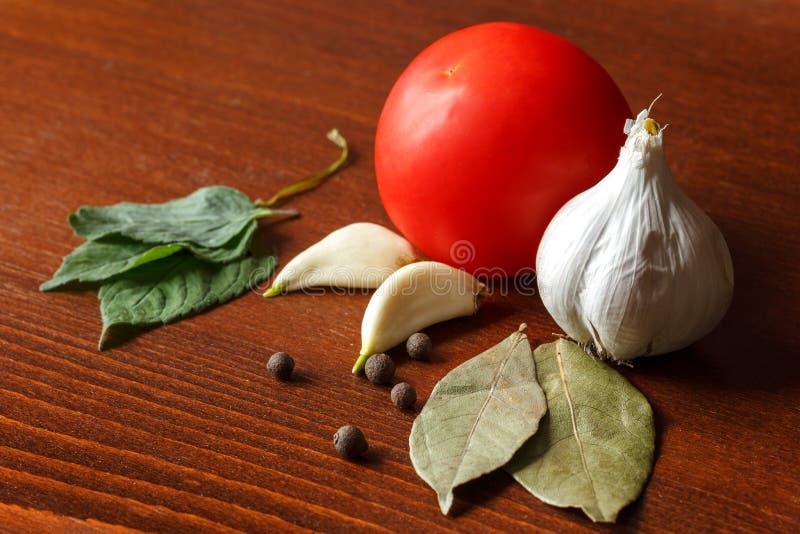 De rode tomaat en het knoflook met kruiden zijn op de lijst royalty-vrije stock afbeelding