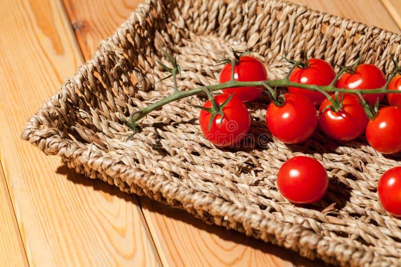 De rode tomaten van de kersenwijnstok zon-gerijpte piccolofluit in rieten mand RT royalty-vrije stock afbeelding