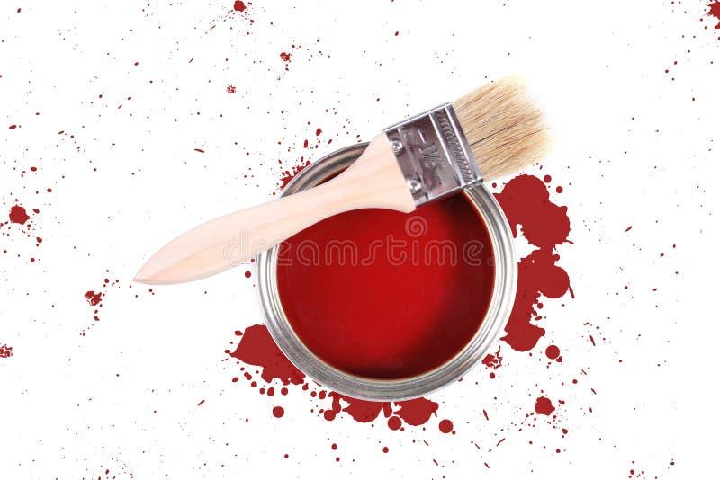 De rode verf kan met borstel en kleurenvlekken stock afbeelding
