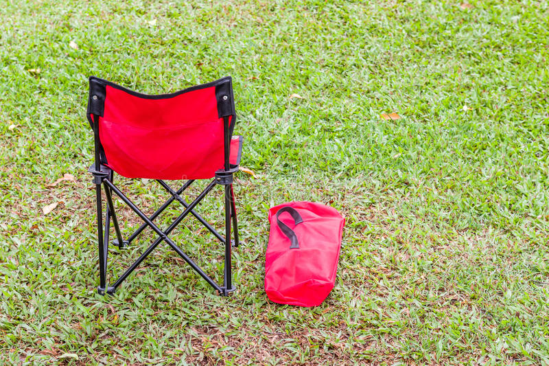 De rode vouwende stoel en de dekking op groen gras stock foto's