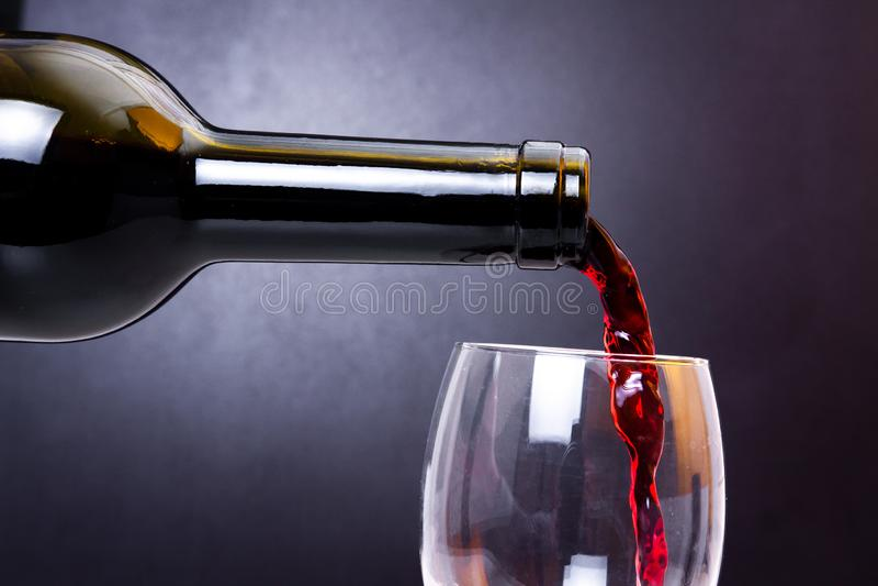 De rode wijn giet in glasclose-up Wijn het gieten aan schoon glas royalty-vrije stock fotografie