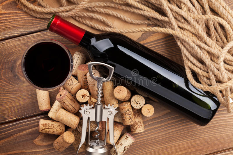 De rode wijnfles, glas, kurkt en kurketrekker Mening van hierboven stock foto's