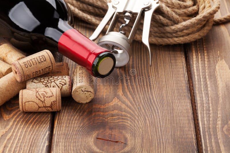 De rode wijnfles, hoop van kurkt en kurketrekker stock afbeelding