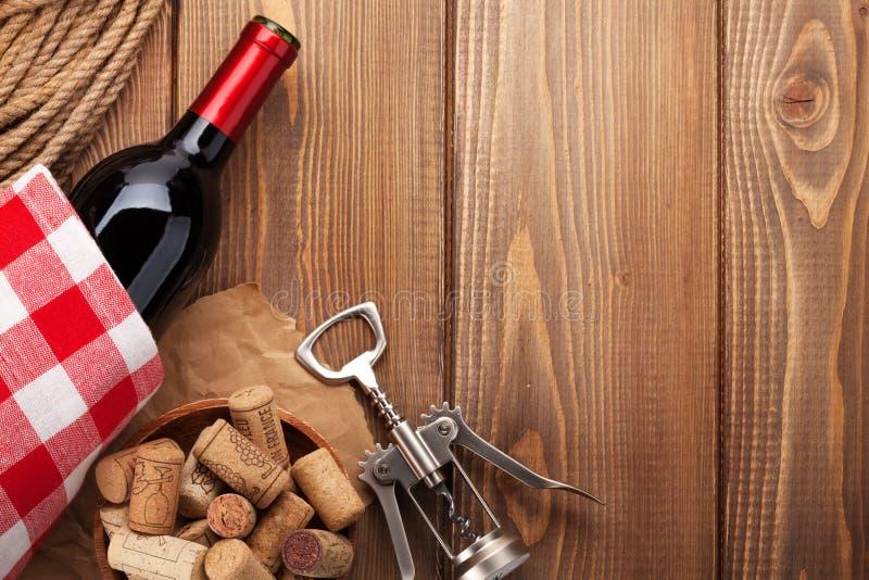 De rode wijnfles, kurkt en kurketrekker over houten lijst backgroun stock afbeeldingen