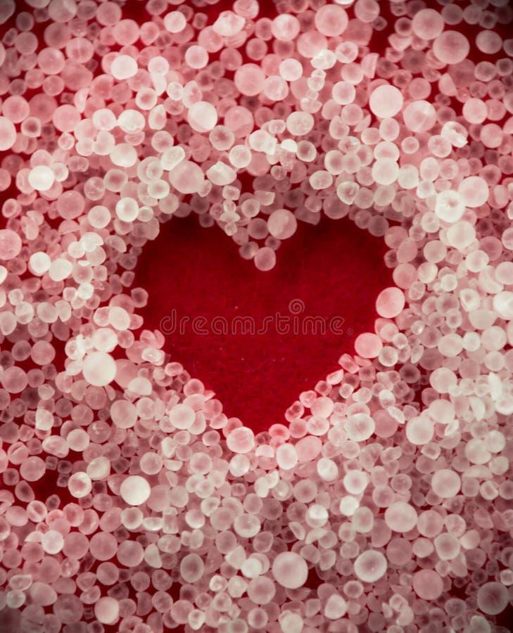 De rode witte transparante zoute kristallen van de hartvalentijnskaart stock foto