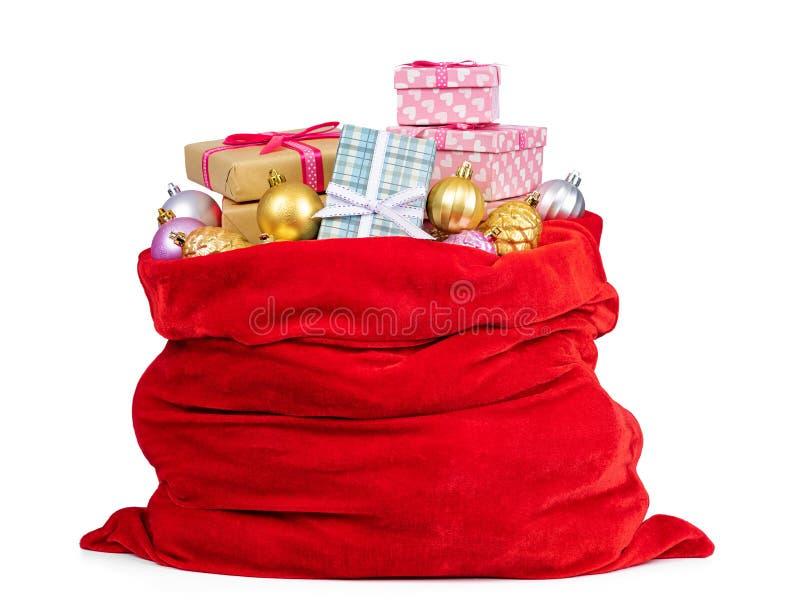 De rode zak van de kerstman vol kerstdozen met geschenken en speelgoed, geïsoleerd op witte achtergrond Het dossier bevat een weg royalty-vrije stock fotografie
