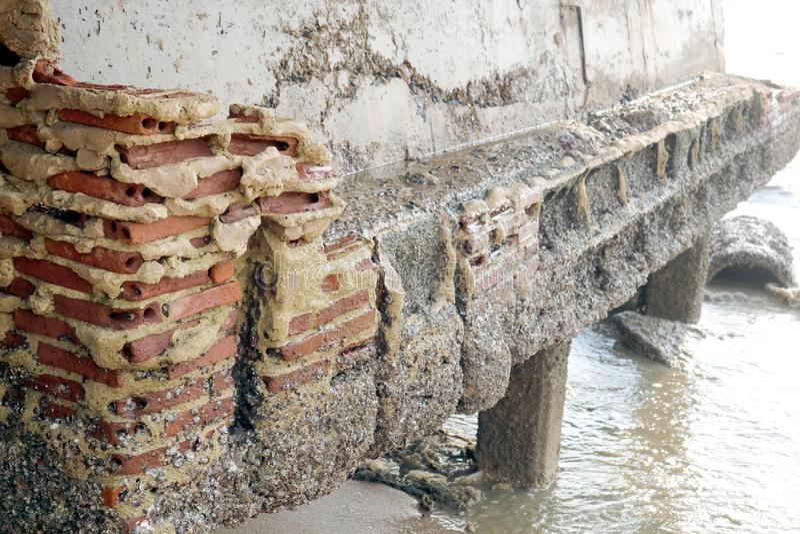 de roest en de erosie van bakstenen muur die op strand voortbouwen waren schade door s royalty-vrije stock afbeeldingen