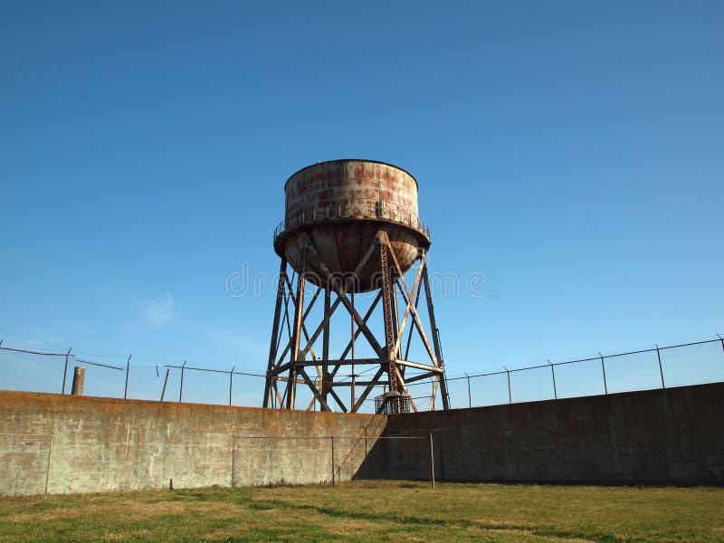 De roestende tribunes van de watertoren voorbij de muur en bard draadomheining royalty-vrije stock afbeeldingen