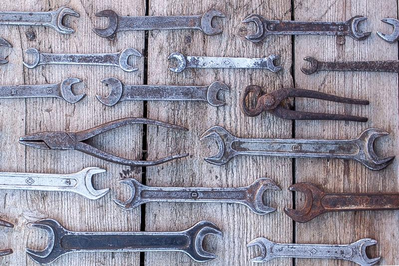 De roestige hulpmiddelen die van de metaalmoersleutel op een zwarte houten lijst liggen Hamer, beitel, metaalzaag, metaalmoersleu stock fotografie