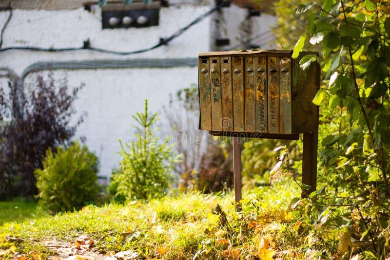 De roestige oude brievenbussen op de de herfstaard Verlaten ijzerbrievenbussen met huisnummers royalty-vrije stock fotografie