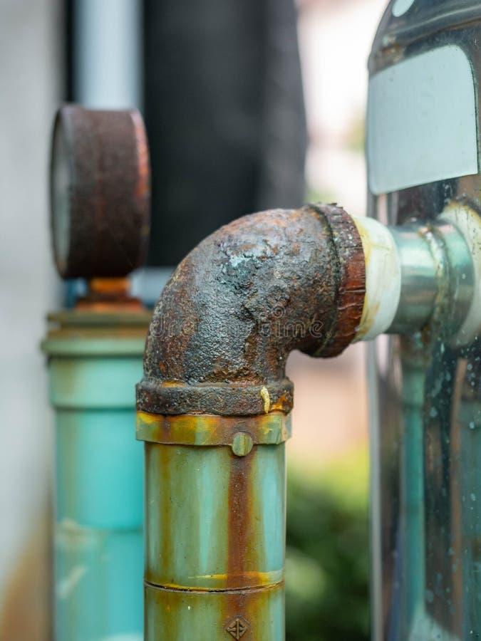 De roestige pijpen van de deur van de waterpomp uit, na vele jaren van verrichting aangetaste metaalpijp werden vernietigd royalty-vrije stock afbeelding