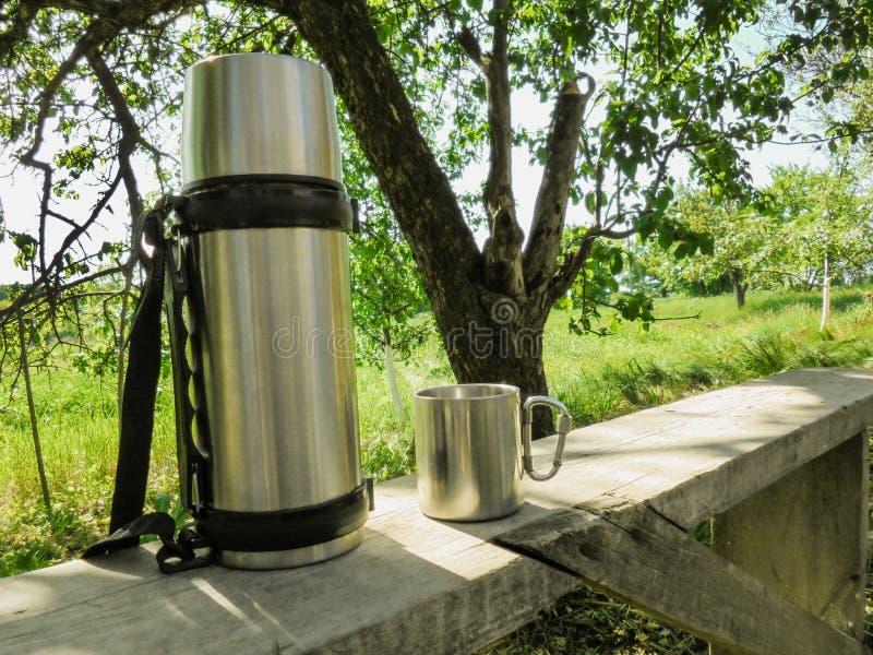 De de roestvrij staalthermosflessen en kop bevinden zich op een bank in de tuin in de zomer stock afbeelding