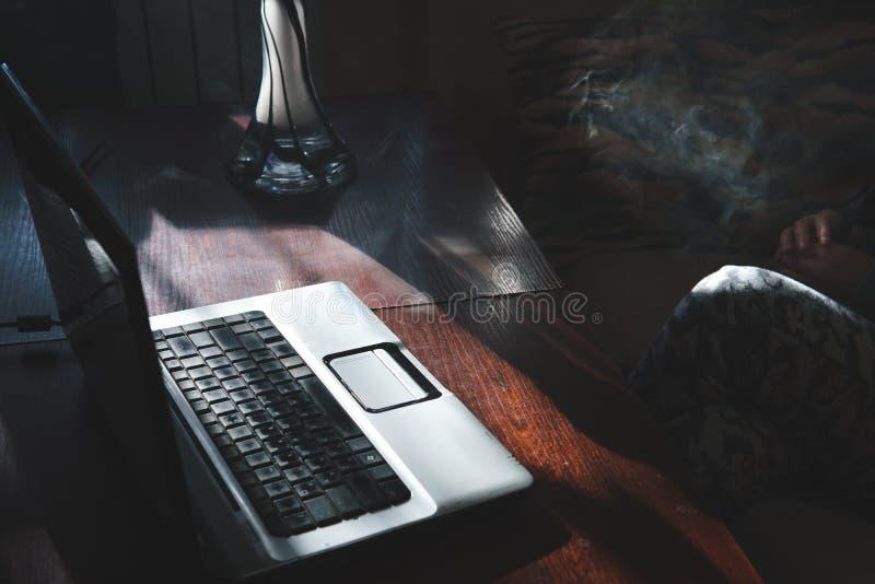 De rokende waterpijp terwijl thuis het werken aan laptop, donker thema, sluit omhoog, zon lichte lijnen stock afbeeldingen