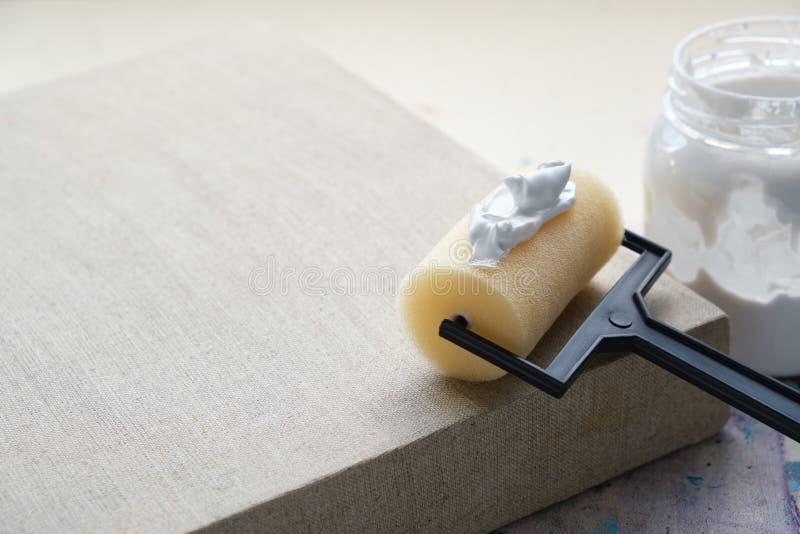 De rol van de kunstenaarsborstel voor canvasdeklaag en linnen artistiek canvas Exemplaarruimte voor tekst stock foto's