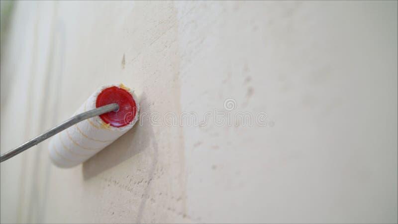 De rol van de muurverf Rolborstel het Schilderen, Arbeider het schilderen bij de rolborstel voor bescherming stock foto's