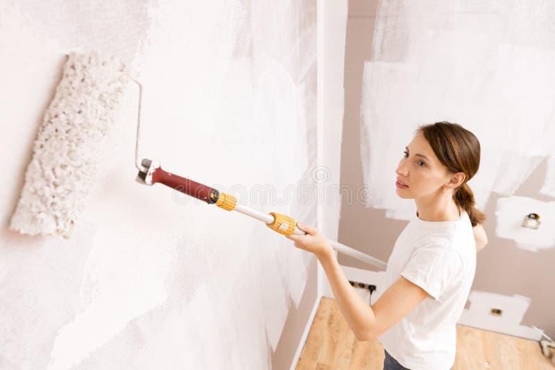De Rol van de verf met verfsteekproeven Mooie vrouw het schilderen muur met verf rolle royalty-vrije stock foto