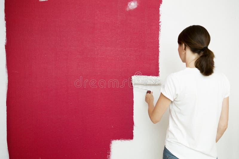 De Rol van de verf met verfsteekproeven Mooie vrouw het schilderen muur met verf rolle stock fotografie