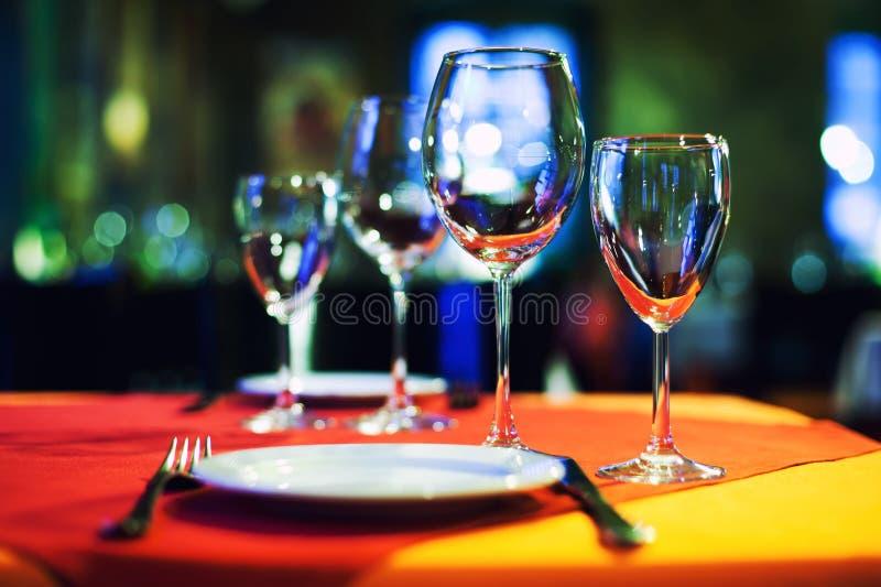 De romantische binnenlandse achtergrond van het koffierestaurant, de gediende glazen van de lijst lege wijn, wit plaat en bestek  stock afbeelding