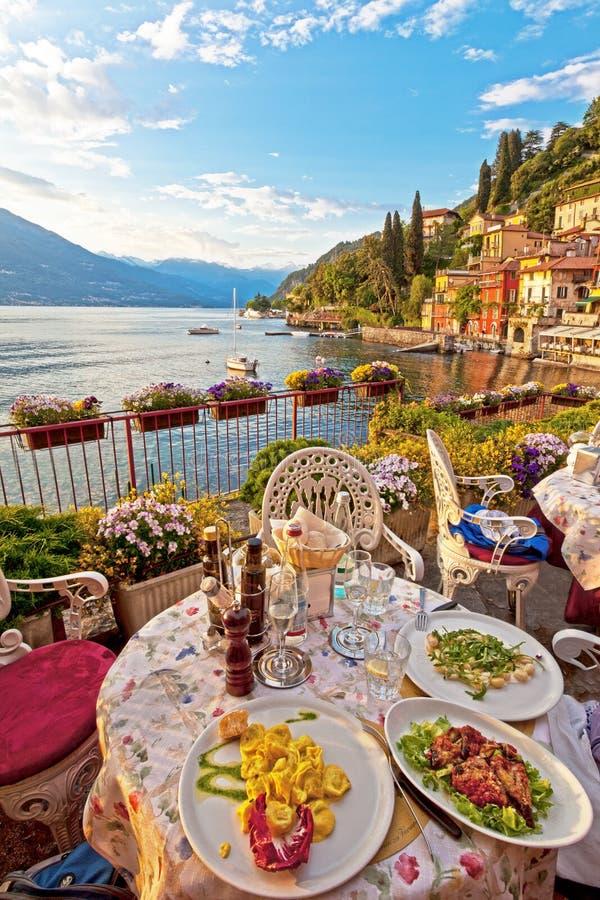 De romantische dinerscène van geplateerd Italiaans voedsel op terras overziet royalty-vrije stock foto