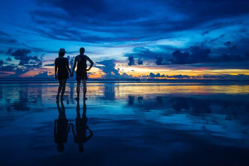 De romantische handen die van de paarholding op de zonsondergang op het strand letten royalty-vrije stock foto's