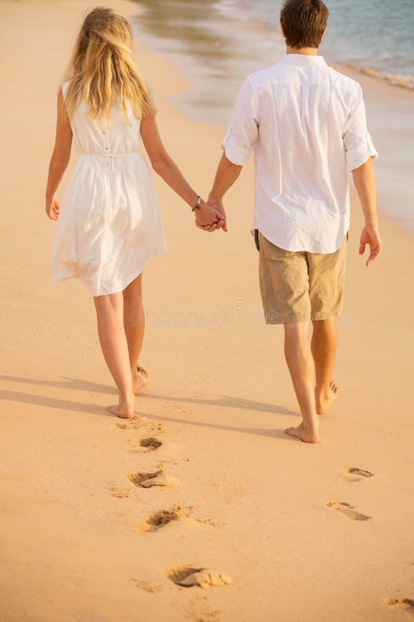 De romantische handen die van de paarholding op strand bij zonsondergang lopen royalty-vrije stock foto