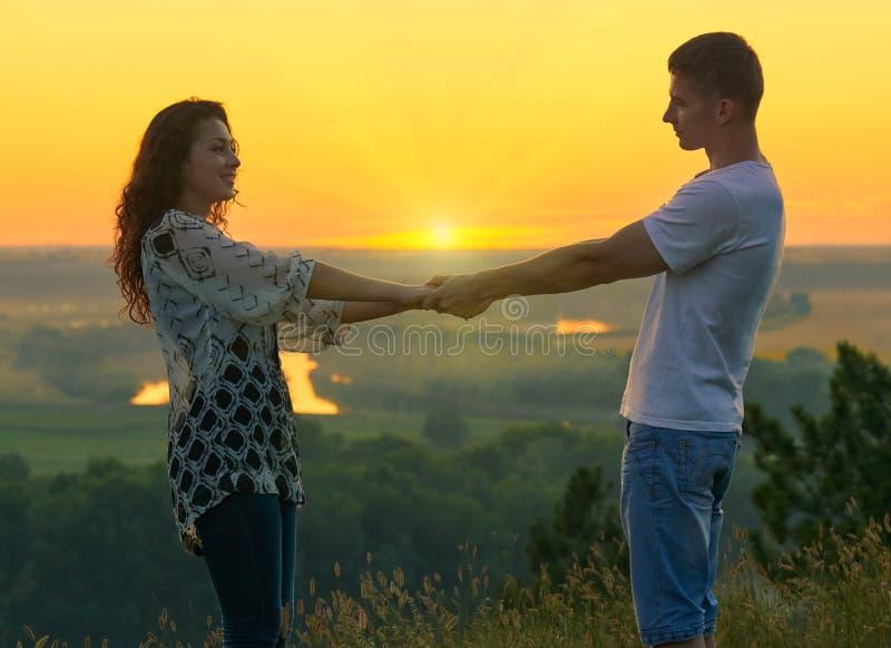De romantische handen van de paarholding bij zonsondergang op openlucht, mooi landschap en heldere gele hemel, het concept van de stock afbeeldingen