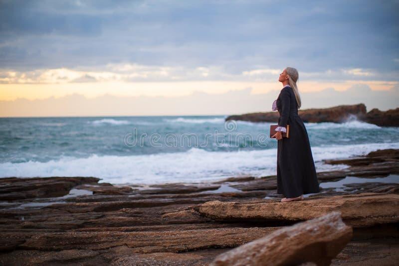 De romantische jonge mooie dame bekijkt in openlucht zonsondergang met een boek in haar hand royalty-vrije stock afbeeldingen