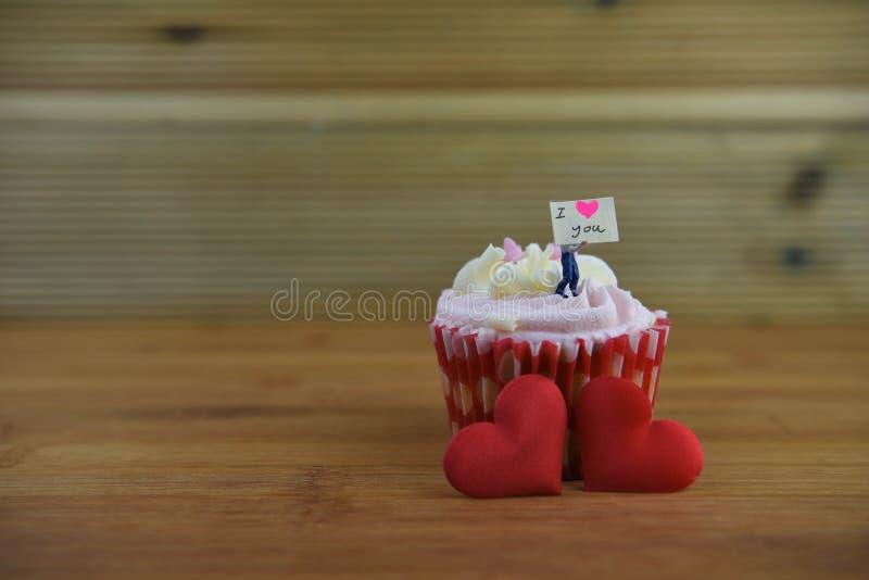 De romantische kopcake in roze en het wit met een miniatuurpersoonsbeeldje die een teken houden schepen op hoogste en rode liefde royalty-vrije stock foto