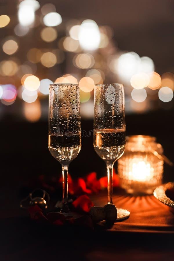 De romantische luxeavond die met champagne met twee glazen plaatst, nam petails en kaarsen toe stock foto