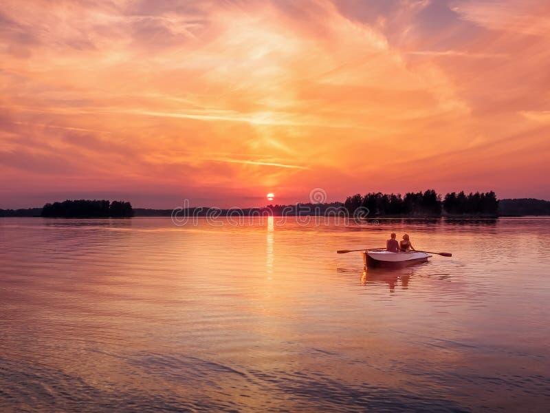 De romantische trillende van de het meermist van de zonsondergangrivier van de het paar kleine roeiende boot houdende van de datu stock afbeeldingen