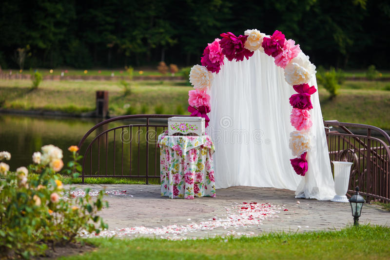 De romantische witte overwelfde galerij van de huwelijksdoorgang met roze bloemblaadjes, bloeit a stock fotografie