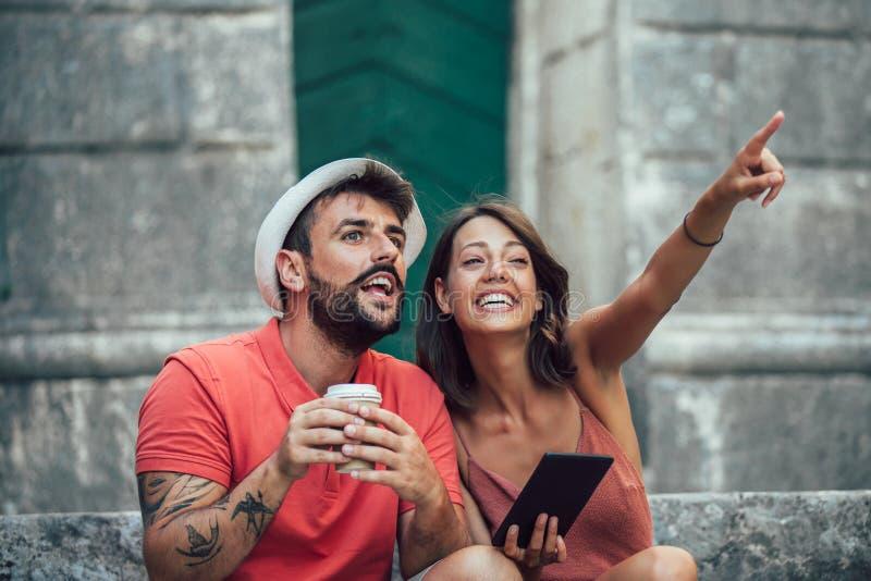 De romantische zitting van het toeristenpaar op treden die digitale tablet gebruiken stock foto