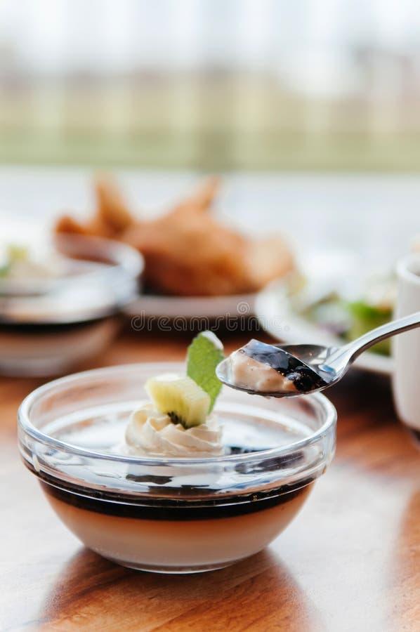 De romige pudding van de vanillekaramel met Kiwi in glaskop op houten Ta stock foto