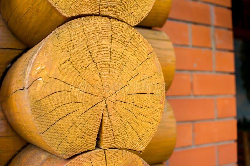 De ronde houten close-up van het logboekhuis met rode bakstenen muurachtergrond stock afbeelding