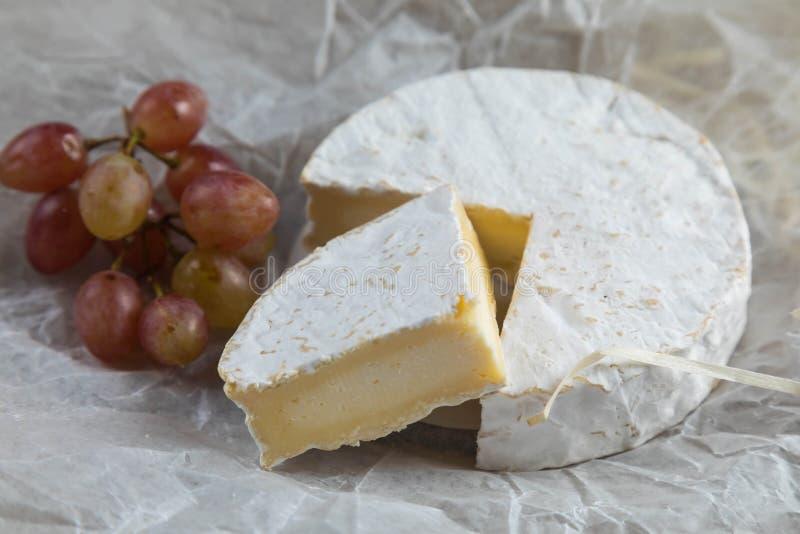 De ronde kaas met een witte vorm wordt gesneden op stukken Op een sectie zijn de korst en de zachtheid van structuur zichtbare bi stock foto's