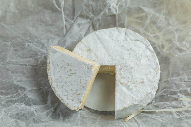 De ronde kaas met een witte vorm wordt gesneden op stukken Op een sectie zijn de korst en de zachtheid van structuur zichtbare bi royalty-vrije stock foto's