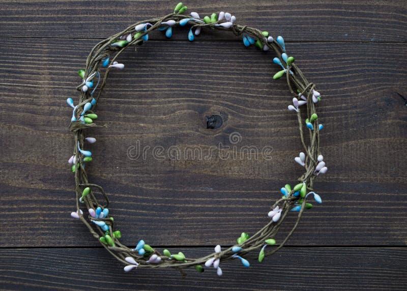 De ronde kroon met kleurrijke parels bij donkere bruine houten vlakke achtergrond, legt, kopieert ruimte stock afbeelding