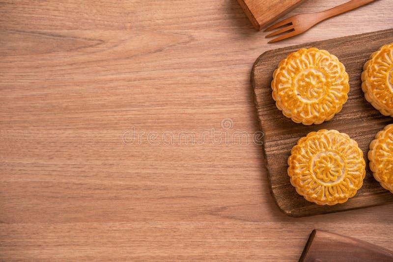 De ronde vormde maancake Mooncake - Chinees stijlgebakje tijdens de medio-Herfstfestival/Maanfestival over houten achtergrond en  stock foto's