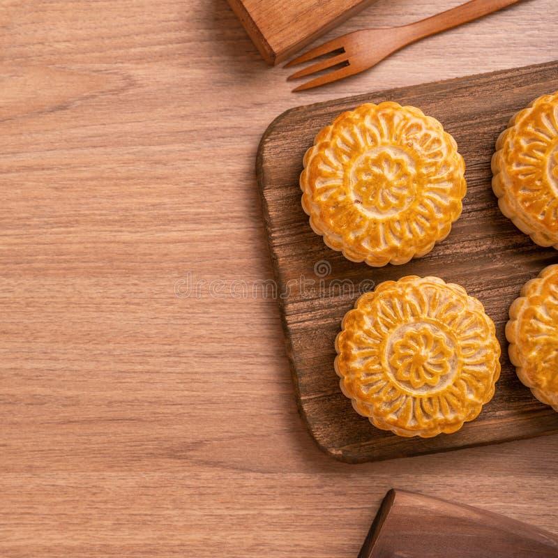 De ronde vormde maancake Mooncake - Chinees stijlgebakje tijdens de medio-Herfstfestival/Maanfestival over houten achtergrond en  stock afbeelding