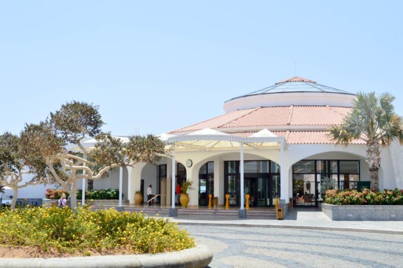 De ronde witte bouw met een dak van rode tegels en glas met een rond bloembed en bomen tegen een blauwe hemel op een zonnige dag  stock foto