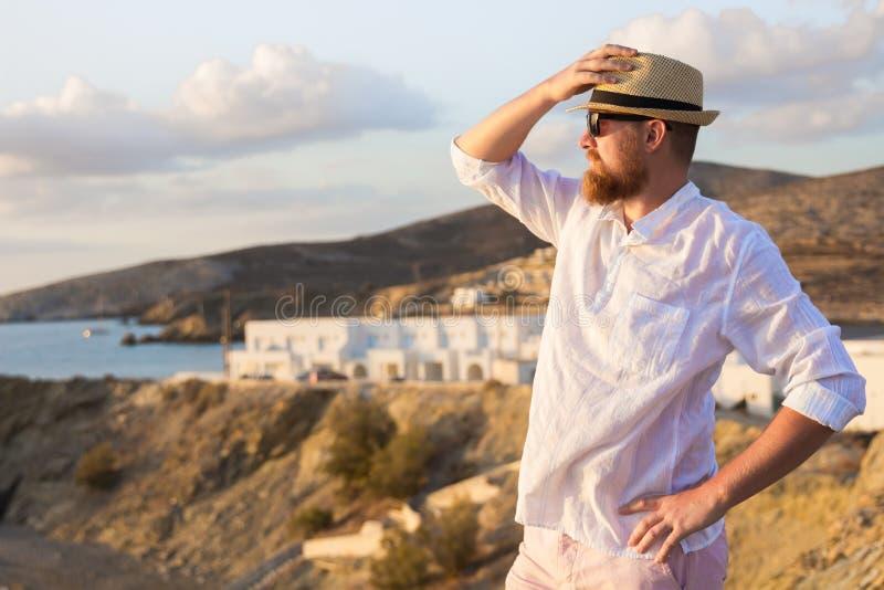 De rood-gebaarde mannelijke reiziger in een wit overhemd bevindt zich in de stralen van de ochtendzon op een steile bank dichtbij stock afbeeldingen