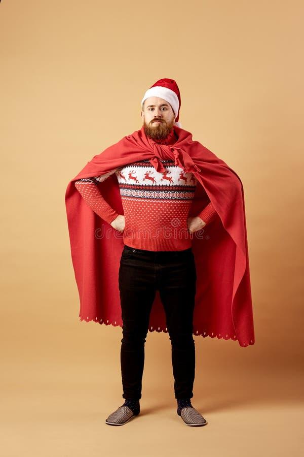 De roodharige mens met baard gekleed in een rode en witte sweater met herten en de rode kaap en dwarsbalkentribunes in stellen va royalty-vrije stock afbeeldingen