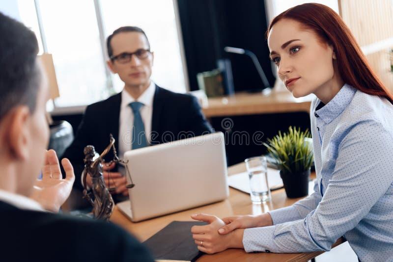 De roodharige mooie vrouw luistert aandachtig aan de mens die scheidingsprocureur bekijken stock afbeelding