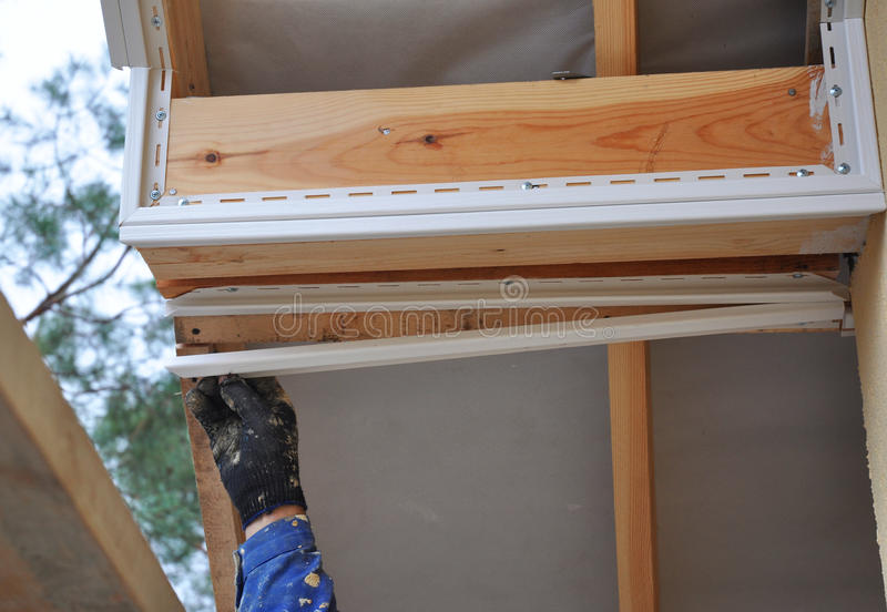 De Rooferarbeider gebruikt een hand om soffit, eaves, houten stralen te installeren stock foto