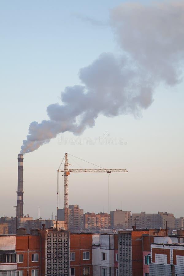 De rook van de boilerpijp boven daken van high-rise flatgebouwen royalty-vrije stock foto's