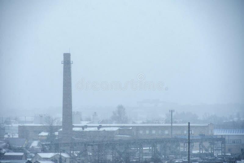 De rook van een grote pijp in een oude fabriek verontreinigt de lucht in de winter stock foto's