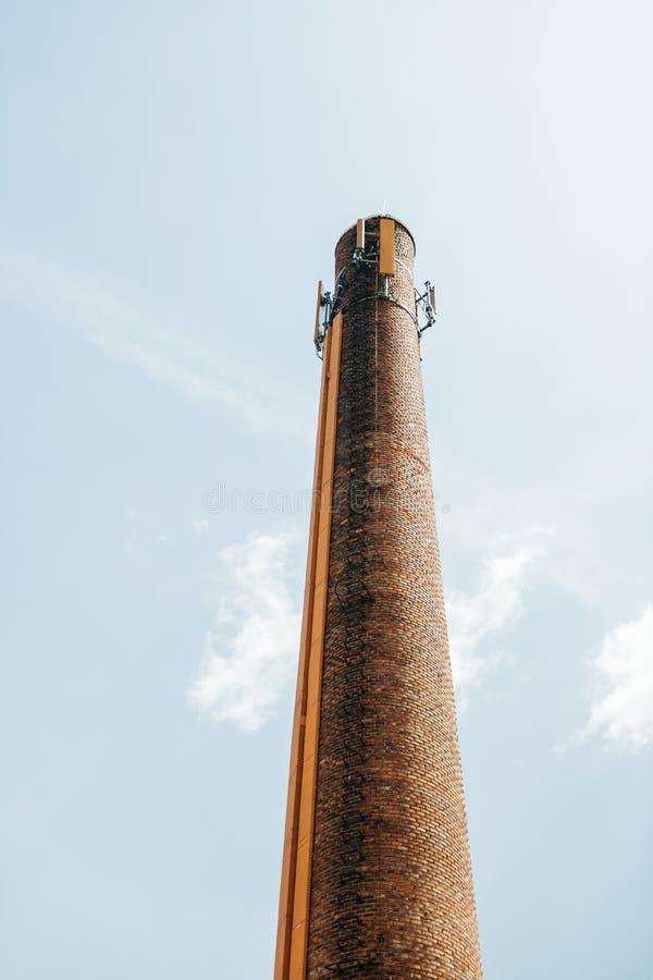 De rookstapel van de schoorsteenbaksteen met mobiele telefoonantenne op bovenkant royalty-vrije stock foto